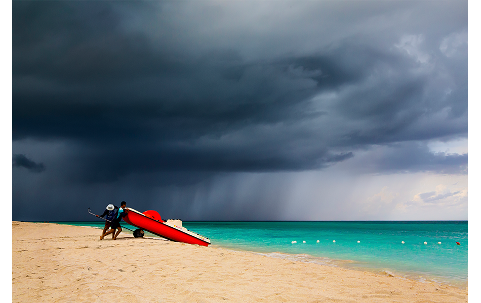 storm approaching beach where two men stand with boat