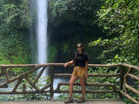 Mackenzie Moore standing in front of a waterfall