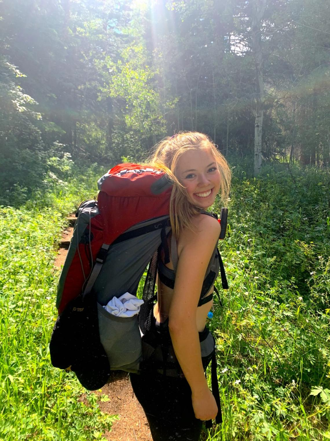 Jeri Wilcox with a backpacking pack on in a forest