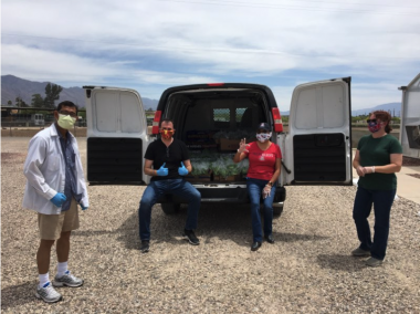 group sitting in van with produce