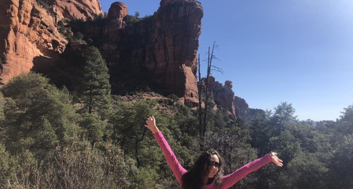 Jaden raising her hands in front of a large rock formation